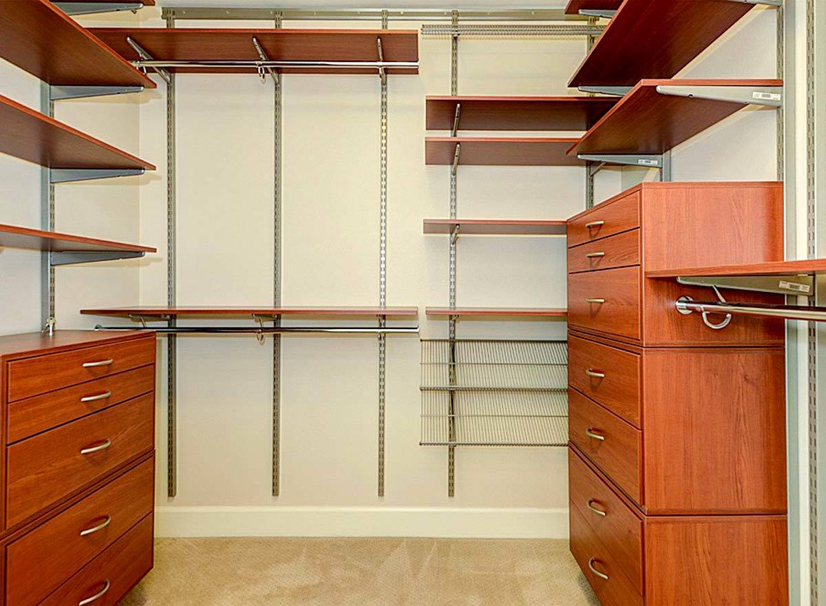Walk-in closet filled with wooden drawers and shelves.