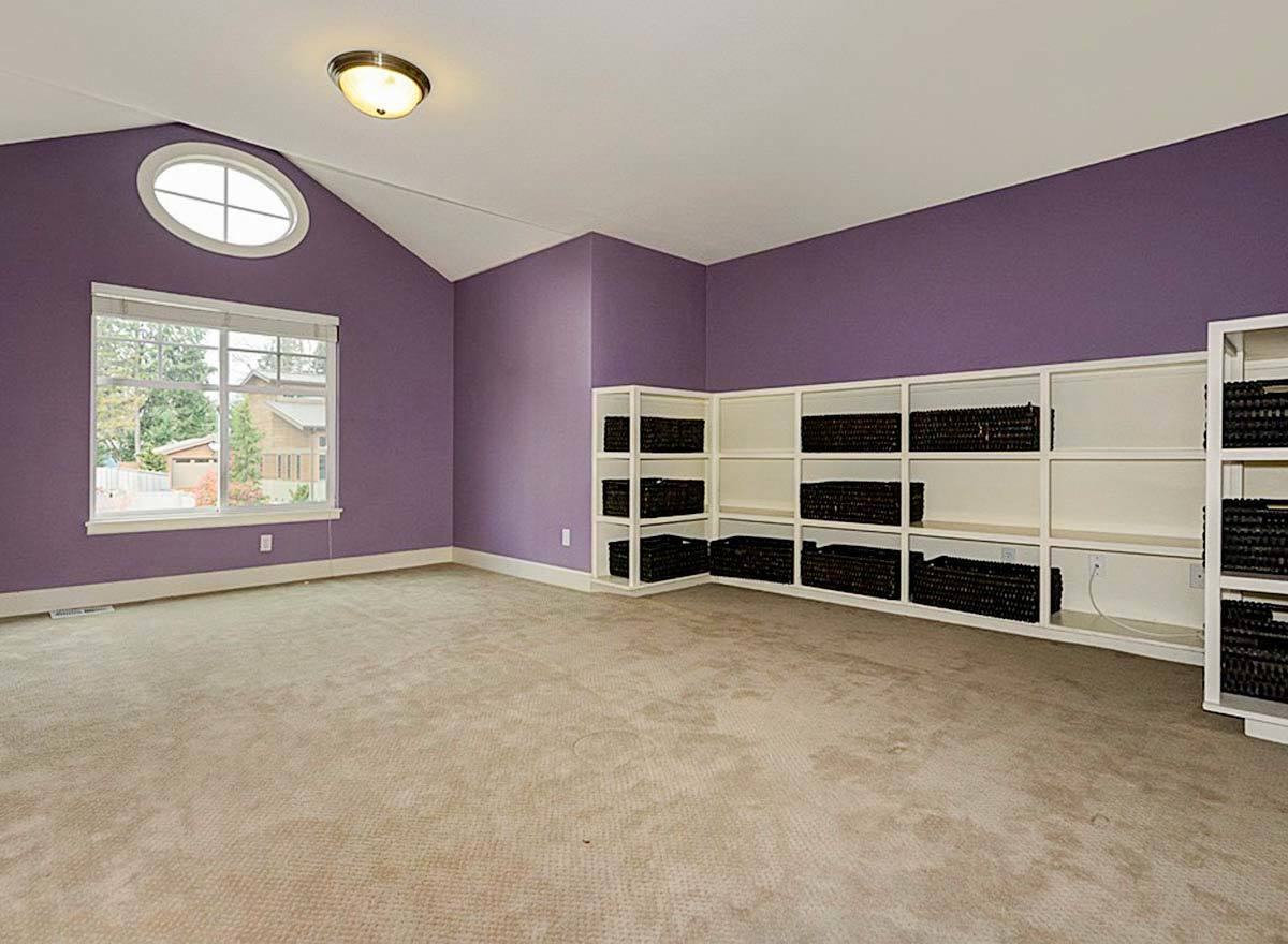 A spacious bonus room with purple walls, vaulted ceiling, and white built-ins.