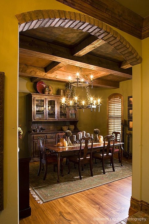 Formal dining room with coffered ceiling, dark wood dining set, and a wooden display cabinet.