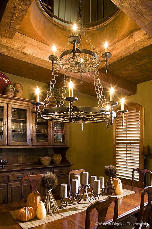 A closer look showing the wrought iron chandelier hanging over the rectangular dining set.