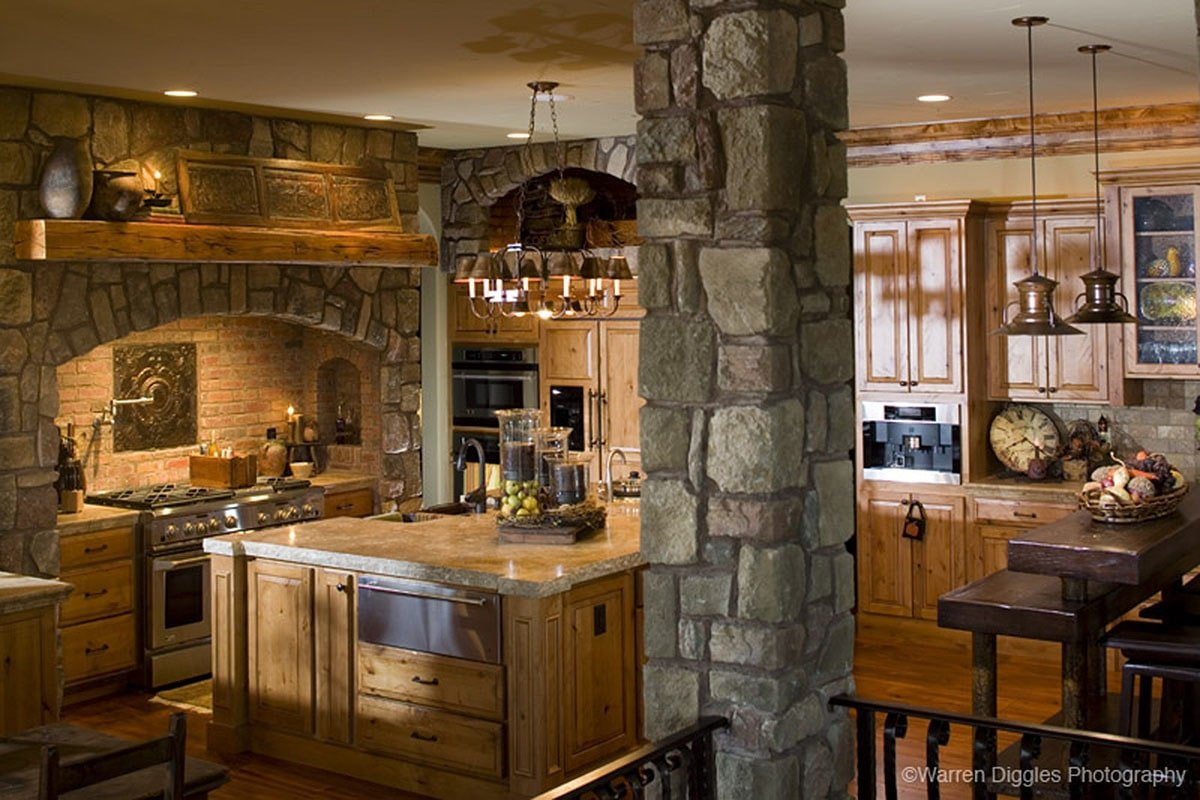 The kitchen has wooden cabinetry, a center island, and a stone column that matches the cooking alcove.