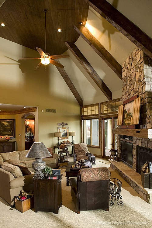 Living room with beamed ceiling, stone fireplace, beige sectional, and brown armchairs.