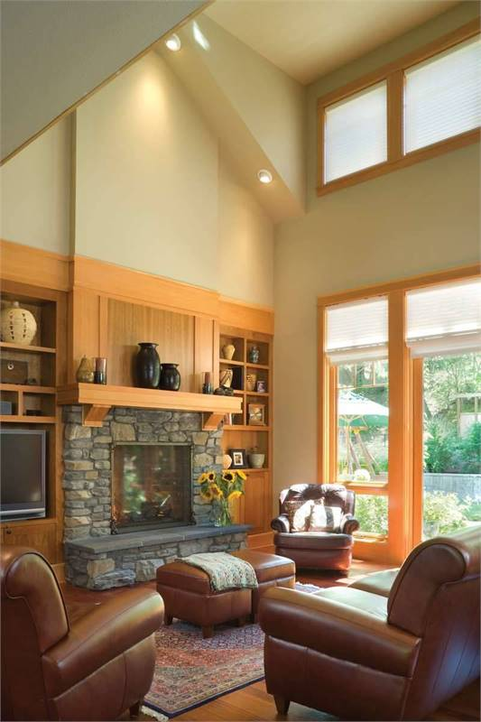 The living room has a soaring vaulted ceiling, clerestory windows, stone fireplace, and brown leather seats.