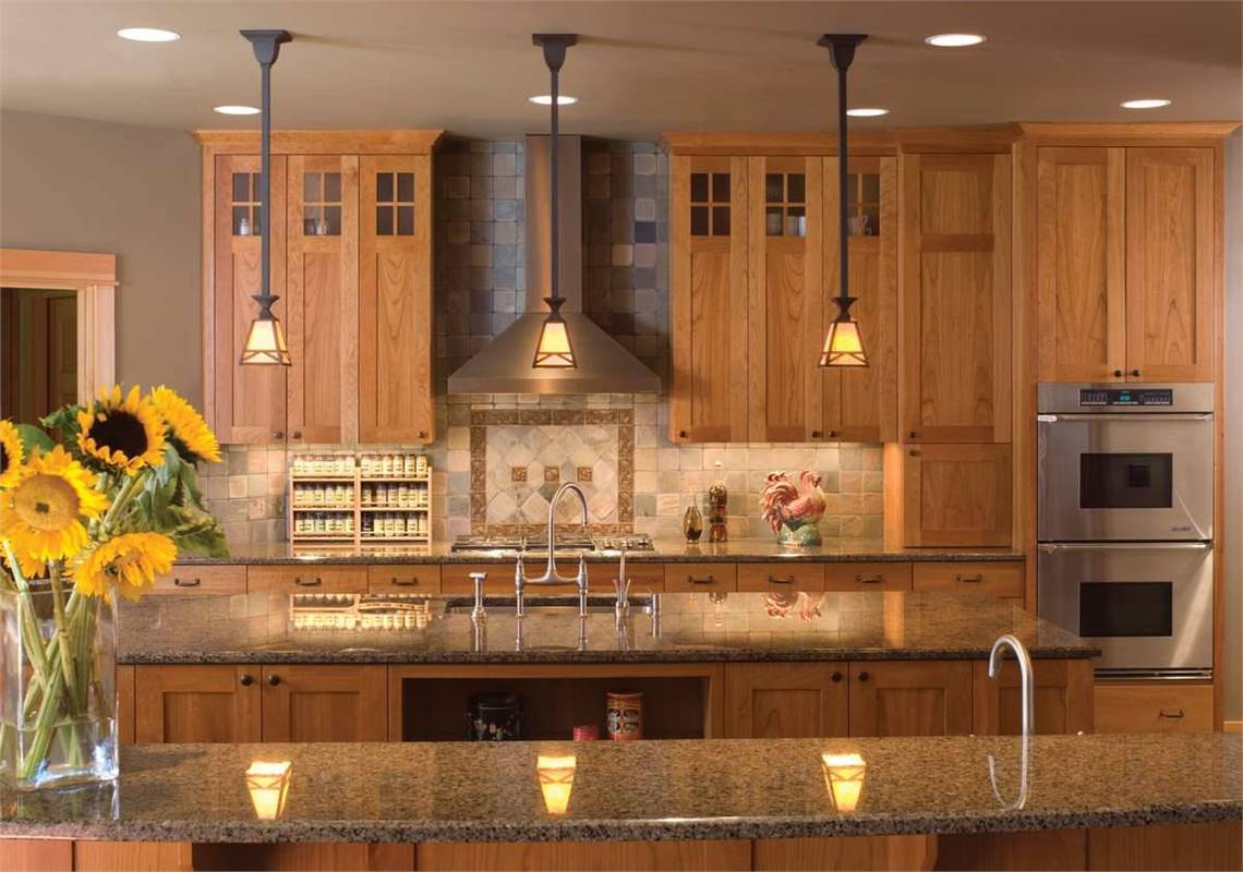 Kitchen with granite countertops, stainless steel appliances, wooden cabinetry, and small glass pendants.