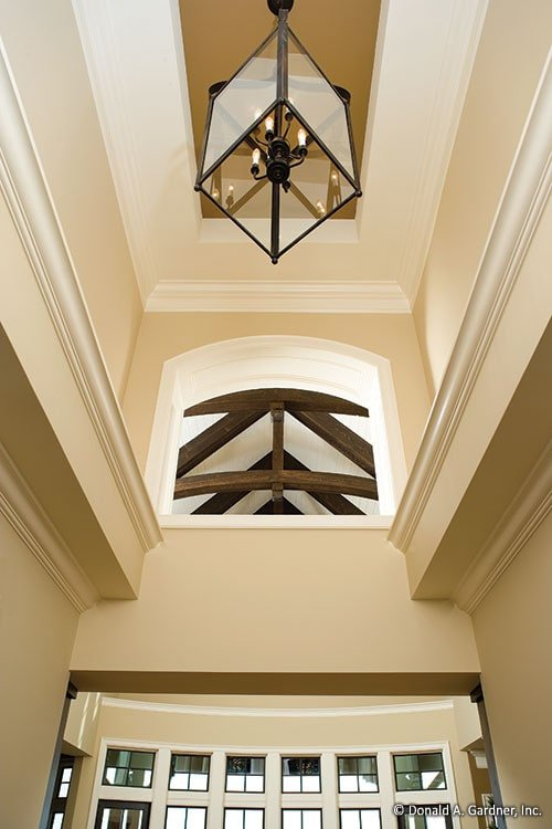 Two-story foyer with a tray ceiling mounted with a glass cube chandelier.