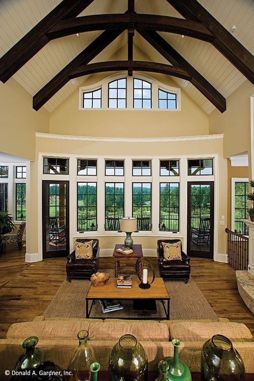 The great room has leather armchairs, beige sectional, bow window, and a cathedral ceiling framed with exposed rustic beams.
