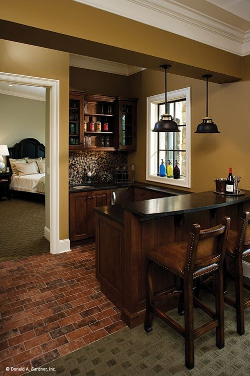 The wet bar has dark wood cabinets, mosaic tile backsplash, and a two-tier counter.