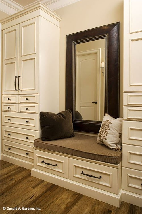 Primary walk-in closet with white cabinets and a built-in bench paired by a large mirror.