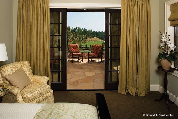 The French door of this bedroom opens to the back porch filled with red cushioned chairs.