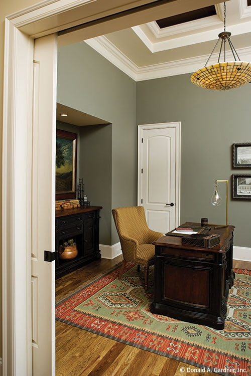 Study with step ceiling, gray walls, and hardwood flooring topped by a bordered area rug.