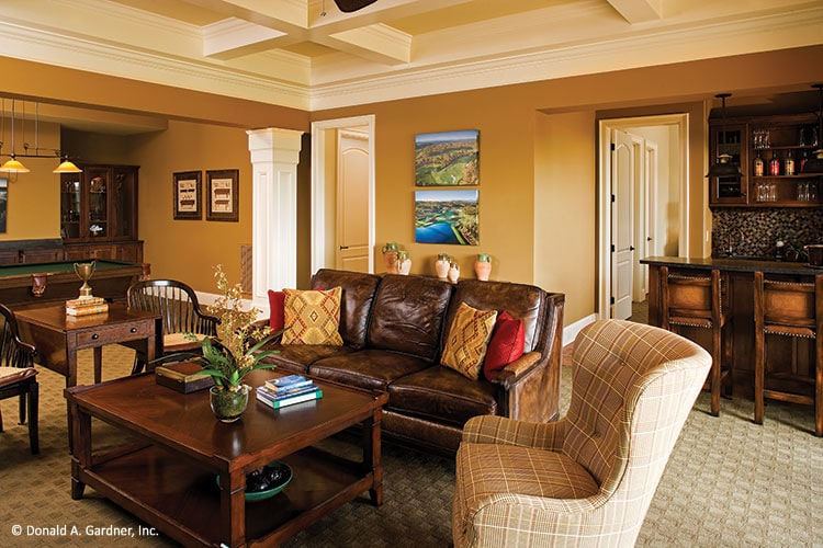 Recreation room with a wet bar, leather sectional, checkered wingback chair, and wooden tables.