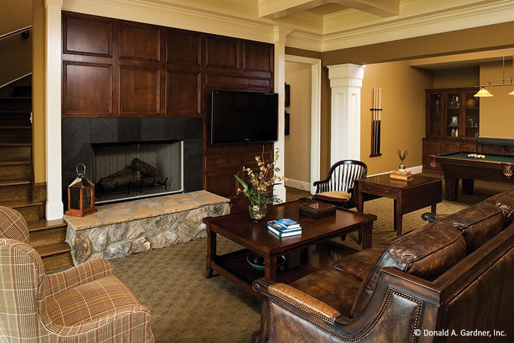 A large fireplace and wall-mounted TV complete the recreation room.