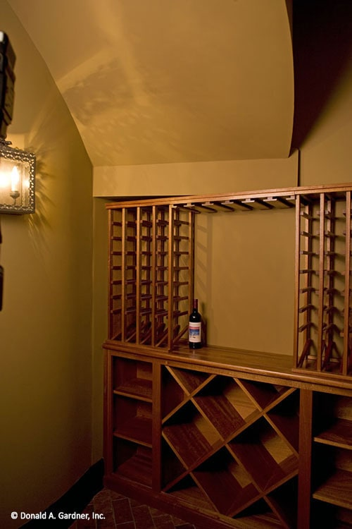 The wine cellar features a wooden wine rack arranged in column and crisscross patterns.