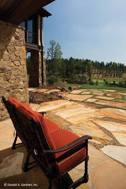 Patio with stone walls, red cushioned seat, and flagstone flooring.