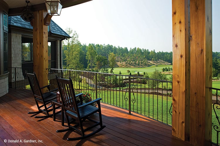 The rear porch has dark wood rocking chairs and wrought iron railings. It overlooks the serene surrounding.