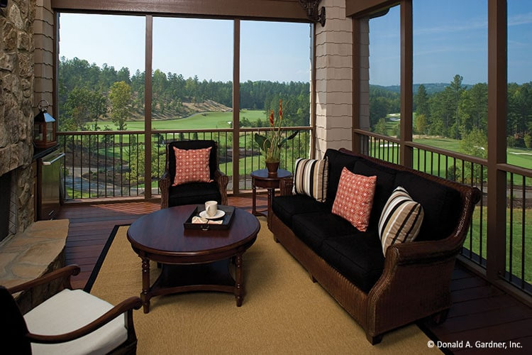 Screened porch with a stone fireplace, round tables, and cushioned seats accented by patterned pillows.