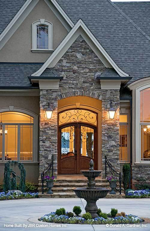Home entry with an arched french door and outdoor sconces mounted on the stone columns.