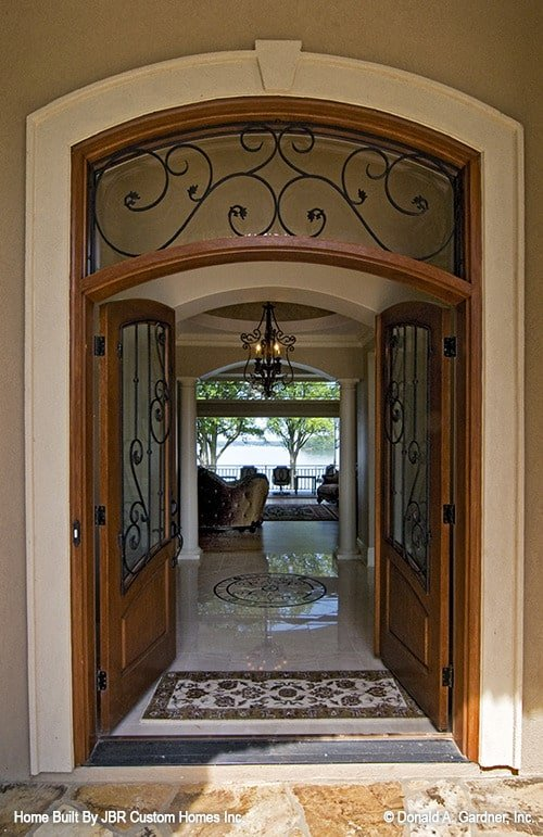 The arched French door opens to the foyer with marble flooring adorned with intricate decals.