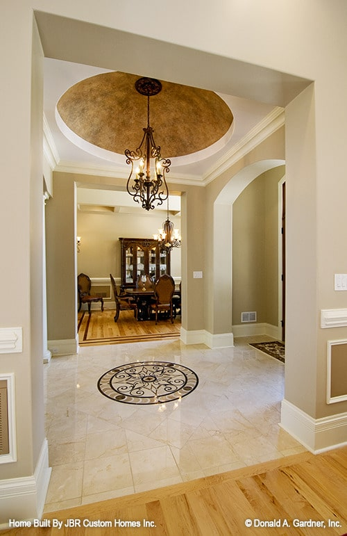 A wrought iron chandelier hanging from the dome ceiling illuminates the foyer.