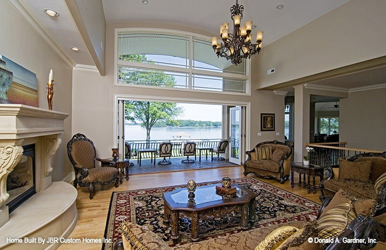 The living room has classy seats, a wooden coffee table, a marble fireplace, and an ornate chandelier.