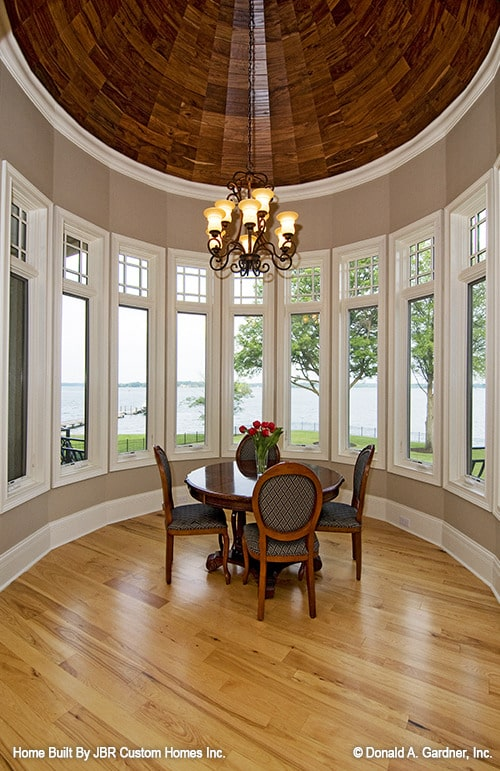 The breakfast nook has a dome ceiling, hardwood flooring, a round dining set, and a bow window overlooking the lake.