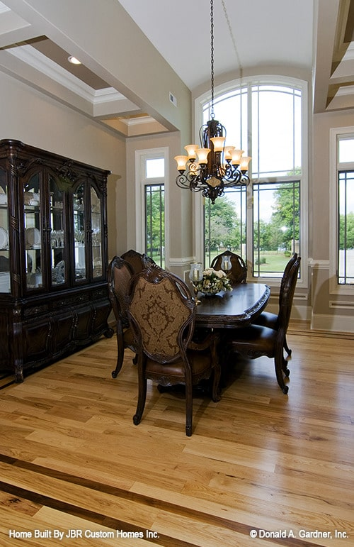 Formal dining room with a barrel-vaulted ceiling, display cabinet, and a dark wood dining set well-lit by an intricate chandelier.