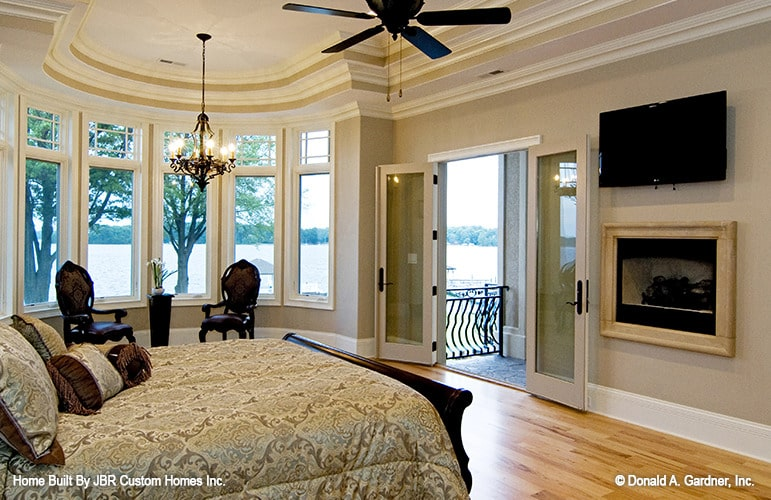 Primary bedroom with a glass-enclosed fireplace, wall-mounted TV, bayed seating area, and private porch access.