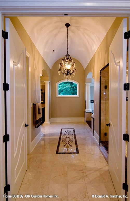 The primary bathroom has its own hallway with marble tiled flooring and a barrel-vaulted ceiling mounted with a crystal chandelier.