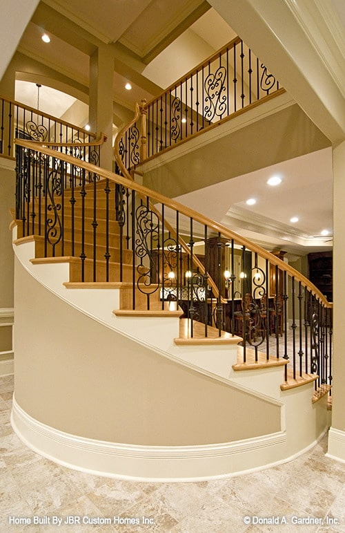 Winding staircase with wrought iron railings and wooden treads leading to the basement.