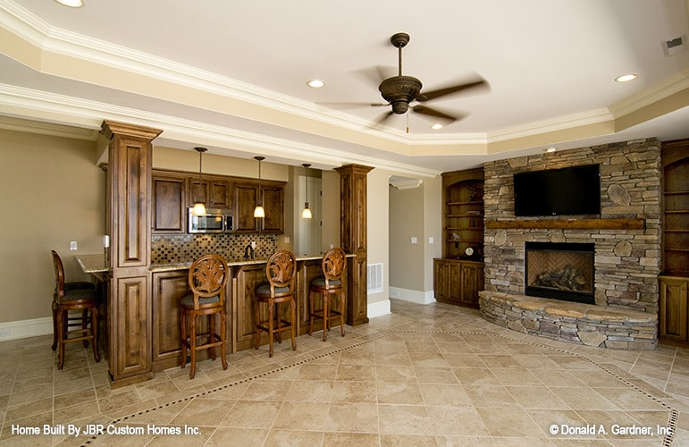 The recreation room has a wet bar and a stone fireplace topped with a wall-mounted TV.
