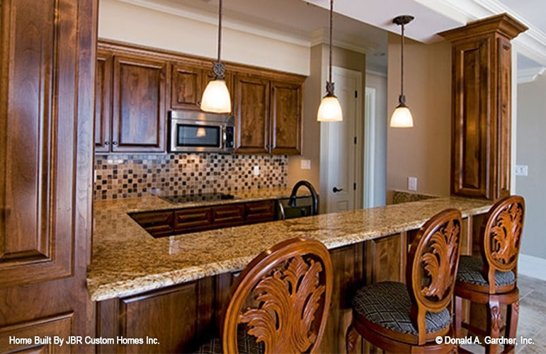 Wet bar with granite countertops, wooden cabinets, and round bar stools.