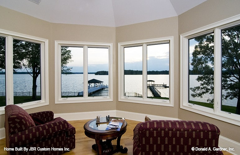 Sitting room with red patterned armchairs, a round side table, and a bay window that takes in a magnificent lake view.