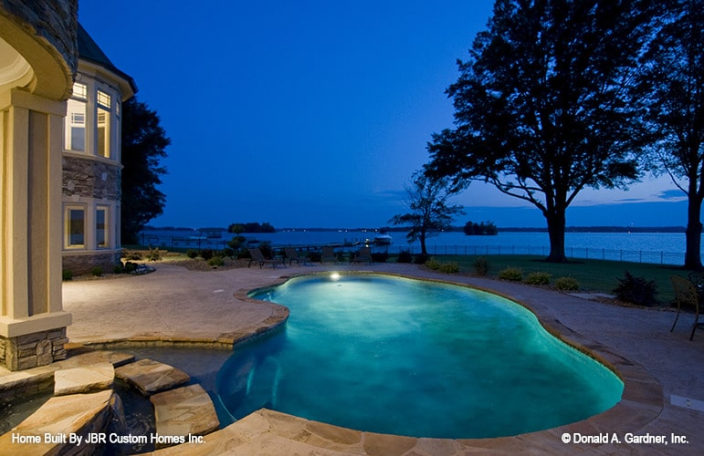 Night view of the freeform pool surrounded by flagstone paving.