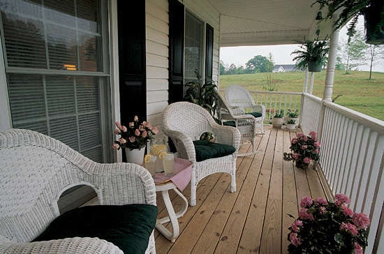 The covered porch is filled with white wicker chairs and metal side tables over wide plank flooring.The covered porch is filled with white wicker chairs and metal side tables over wide plank flooring.