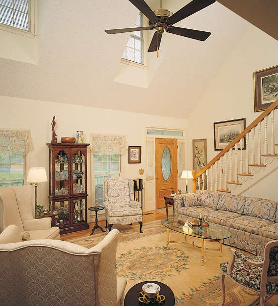 Living room with vaulted ceiling, floral sectional sofa, wingback chairs, and a classic area rug.