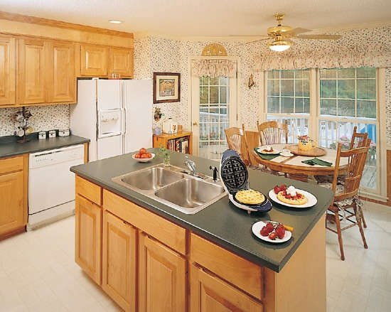The eat-in kitchen is equipped with white appliances, double bowl sink, prep island, and a round dining set.