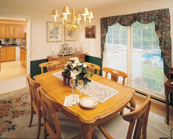 Formal dining room with cushioned chairs and a wooden dining set well-lit by a gilded chandelier.