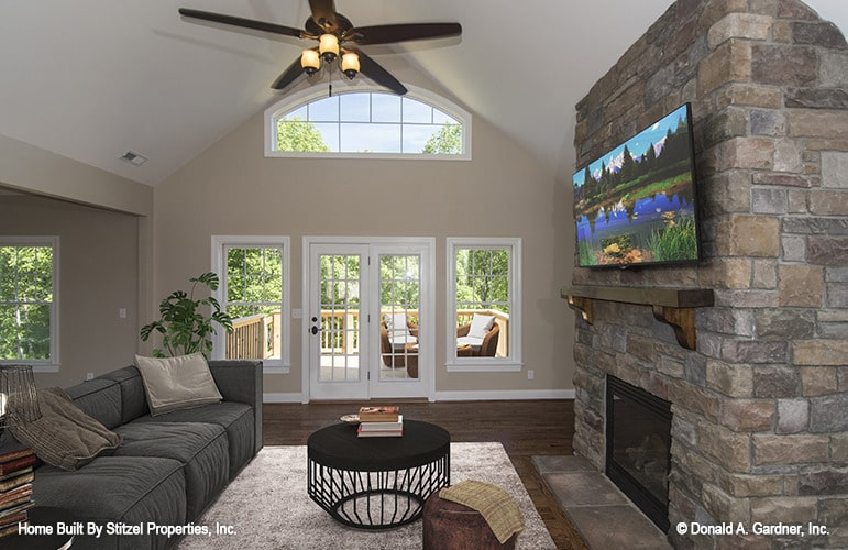 The living room has a cathedral ceiling, stone fireplace, gray sectional, and a glass door that opens to the deck.