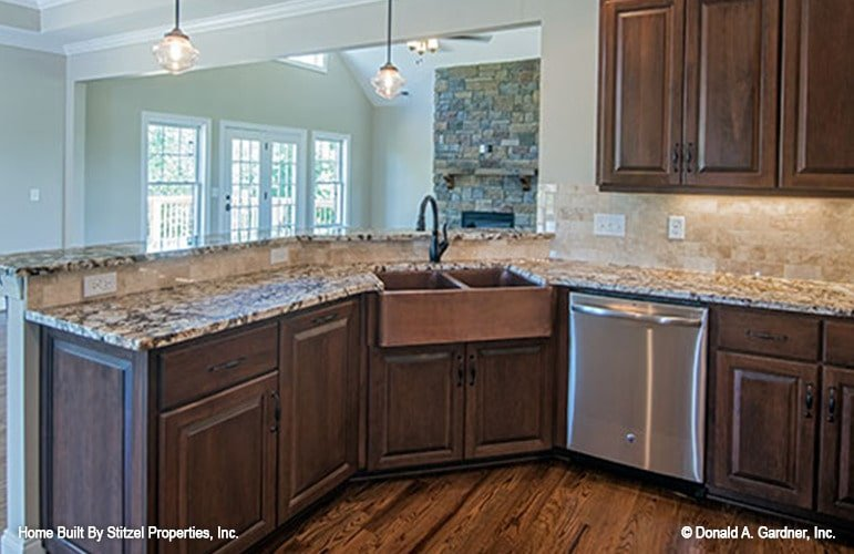 The kitchen peninsula is fitted with a farmhouse sink, dishwasher, and two-tier granite countertops.