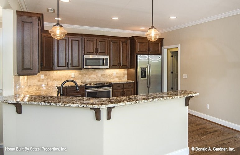 A pair of glass pendants along with recessed ceiling lights illuminate the kitchen.