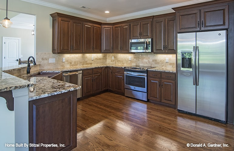 The kitchen offers wooden cabinetry, stainless steel appliances, and granite countertops.