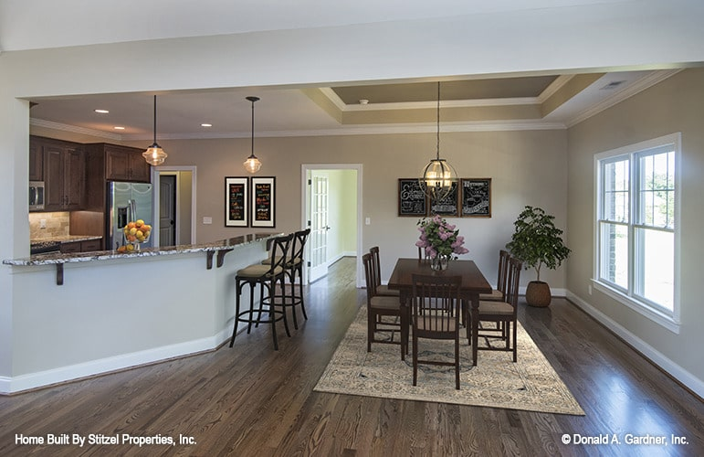 The dining area has a spherical chandelier, rectangular dining table, and cushioned chairs sitting on a patterned area rug.