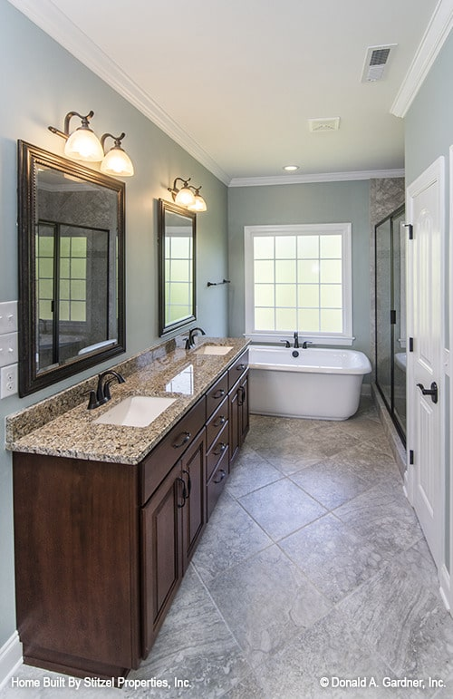 The primary bathroom is equipped with his and her vanity, freestanding tub, toilet room, and a walk-in shower.