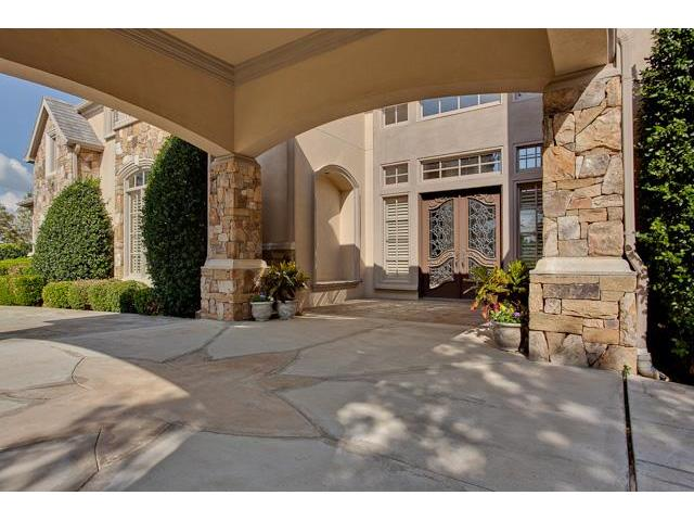 Covered entry with huge stone columns, arched inset, and a french door.