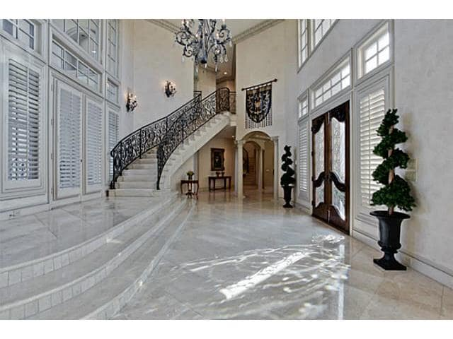 Spacious foyer with trimmed plants, grand chandelier, and an elaborate curved staircase.