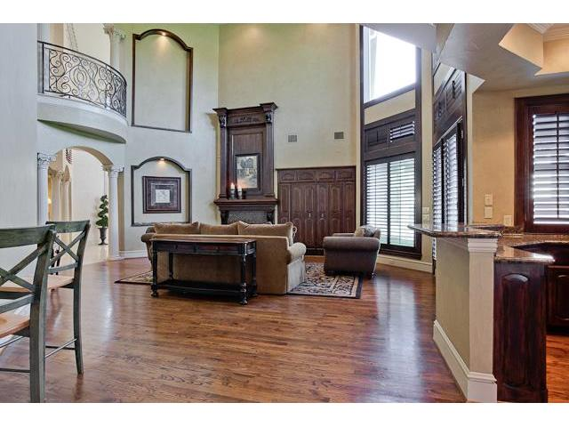 The living room has brown seats, wooden tables, built-in cabinets, and a fireplace.