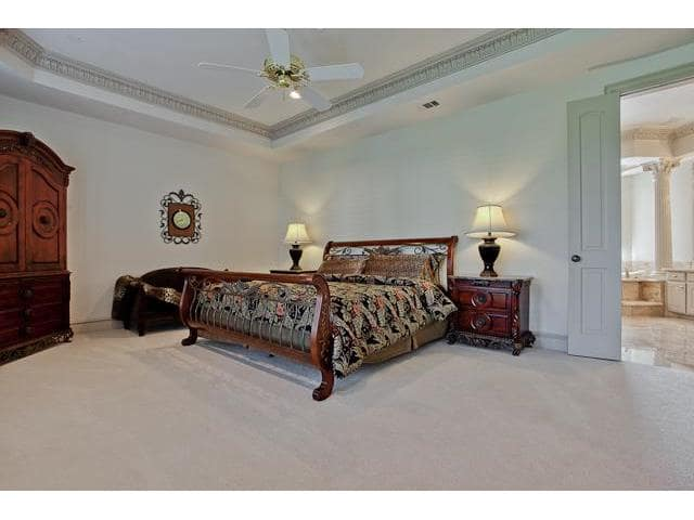 This bedroom has dark wood furnishings, beige carpet flooring, and a tray ceiling mounted with a brass ceiling fan.