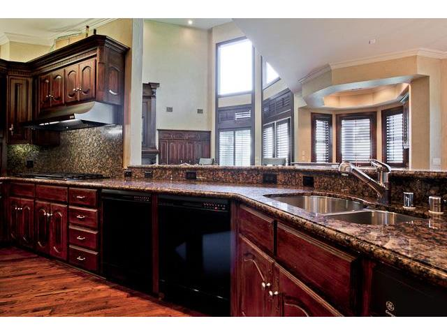 Kitchen island with granite countertops and a double bowl sink.