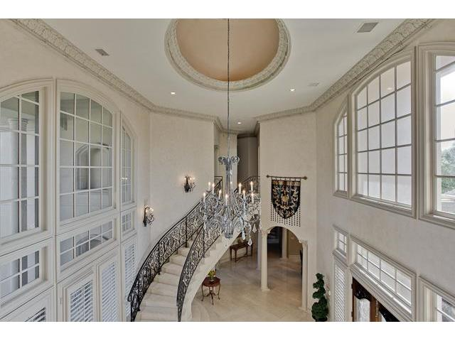 Another view of the foyer showing the arched transom windows and a round tray ceiling.