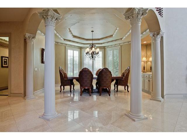 Formal dining room defined by greek columns. It has classy patterned chairs, wooden dining table, and an ornate chandelier.